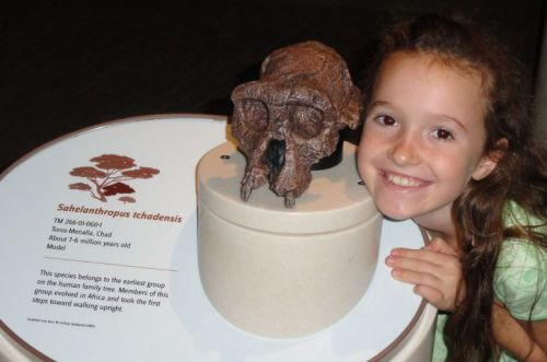 my daughter Leilani with Sahelanthropus tchadensis skull at Smithsonian